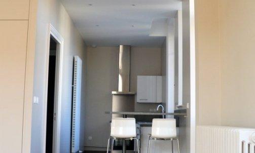 Simplement délimitées par le mange-debout et la différence de revêtement de sol, les cuisines offrent une profondeur visuelle depuis la pièce à vivre.