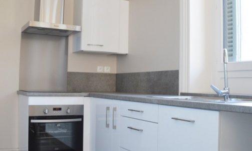 Aménagées en L, les cuisines équipées offrent une belle surface de travail tandis que le mange-debout permet d'opérer la transition avec la pièce à vivre. Meubles LAPEYRE, plan de travail mélaminé POLYREY