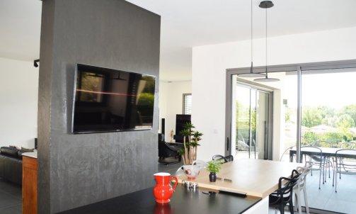 Habillé en béton ciré, le mur de séparation entre la cuisine et le salon sert de pivot entre les différents espaces. Béton ciré Macadam CB 05, COULEURS D'ANTAN