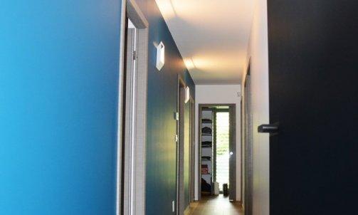 Menant aux chambres, une des face du couloir a été peinte en bleu afin de rythmer cet espace. Peinture : Bleu Jambi CH1 0897, nuancier CHROMATIC / SEIGNEURIE