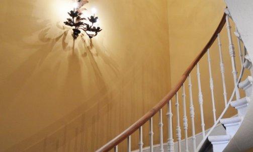 La cage d'escalier a été traité dans un style anglais, murs jaunes et boiseries blanches. Réalisées sur-mesure, les appliques habillent les murs et reflètent l'identité des lieux.