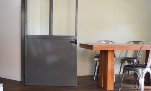 Au salon, un pan de mur se pare de Vert Keruing CH1 0963 (Seigneurie) en accord avec la nouvelle verrière peinte en RAL 7022 et les différentes tonalités de bois.
