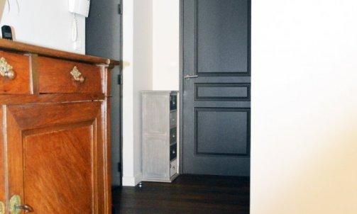 Le couloir gagne en luminosité grâce au Beige Brêche CH1 0977 appliqué sur l'ensemble des murs et à la création de la verrière dont le rappel de couleur est fait sur les portes.