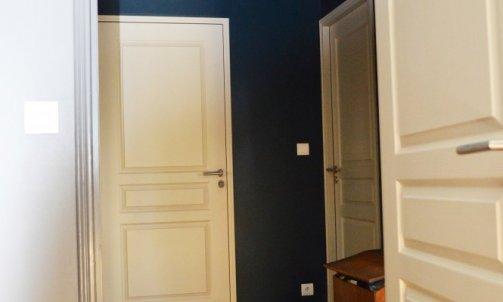 Dans le dégagement, un bleu soutenu, Bleu Mayotte CH1 0900 (Seigneurie) est appliqué aux murs et au plafond pour en faire un véritable élément de passage vers les chambres. Peintes en Beige Brêche dans la continuité du reste de l'appartement, les portes viennent rythmer cet espace.