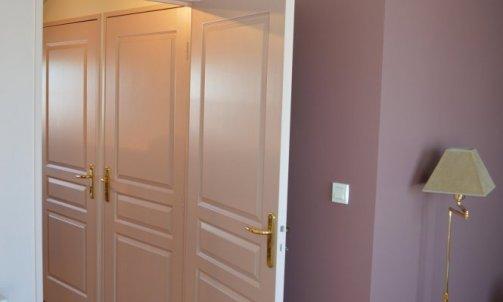 Dans la chambre principale, l'alcôve existante est renforcée par une teinte poudrée, Brun Manitoba CH1 1027 (Seigneurie), tandis que le reste des murs et des boiseries est peint en Beige Minérale CH1 0318 (Seigneurie).