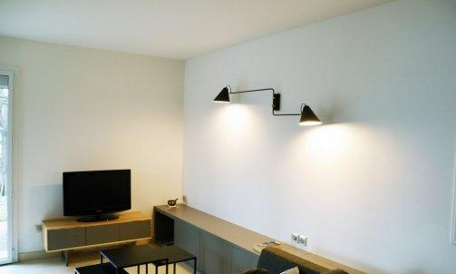 L'espace salon s'organise autour du banc qui devient à la fois une assise supplémentaire ou un espace de rangement.