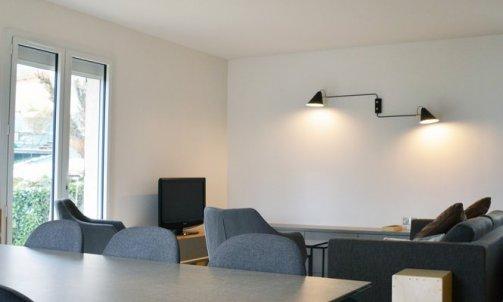 Minimaliste, l'espace salle à manger se définit par la table, les chaises et la suspension. Table Akil, MIDJ / Chaises fournies par les clients / Suspension Acrobates, DCW EDITIONS.
